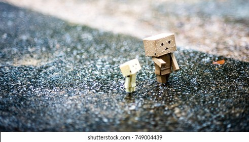 Family Concept : A Danbo walking on the road after the rain