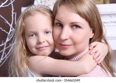 Family concept. Mom and daughter sit hugging. Blondes.