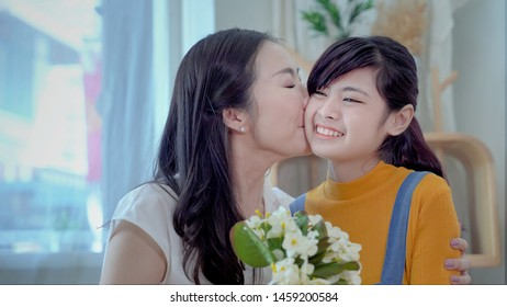 Family concept, mother and daughter are showing love each other by kissing. South East Asian families