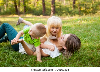 Family concept, mother and her daughter and son together playing and laughing on the grass