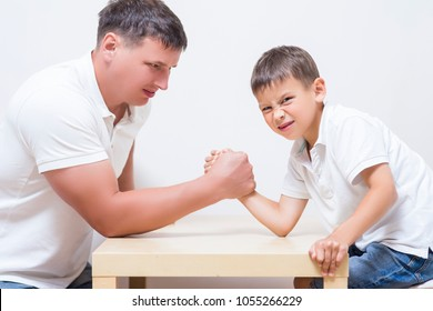 Family Concepts. Father is Having Funny Armwrestling Tournament with His Little Son Indoors. Horizontal Shot