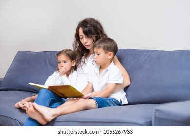 Family Concepts. Mother with Two Children Reading a Book Together on Couch Indoors.Horizontal Image Composition