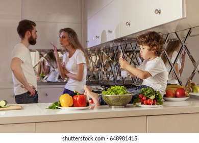 Family conflict photo. Little boy sitting on the kitchen surface while his parents fighting on the background.