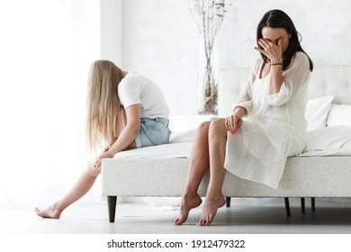 Familienkonflikt und Beziehungskonzept. Mutter und Tochter, die sich streiten und zuhause zugeben. Traurige Frau und jugendliches Mädchen, die auf dem Bett sitzen. Nicht einander ansehen.