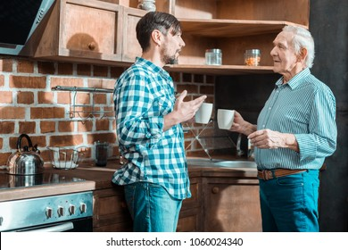 Family conversation. Pleasant nice brunette man looking at his father and talking while standing with him in the kitchen