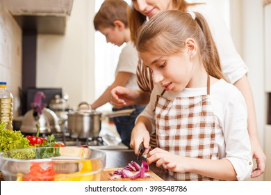 Family cooking background. Mum and daughter cutting onion for salad in the kitchen