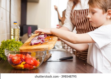 Family cooking background. Small boy help his mother with cutting onion for salad in the kitchen