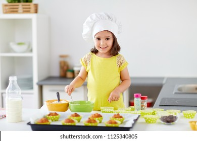 family, cooking, baking and people concept - happy little girl in chefs toque making batter for muffins or cupcakes at home kitchen