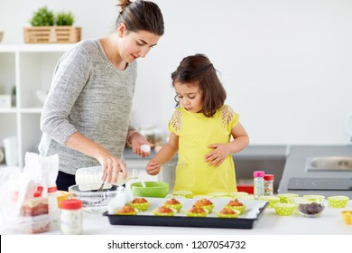 family, cooking, baking and people concept - happy mother and little daughter pouring milk into bowl and making batter for muffins at home kitchen