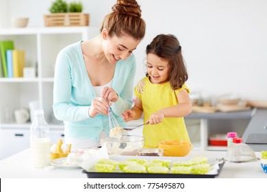 family, cooking, baking and people concept - happy mother and little daughter making batter for muffins at home kitchen