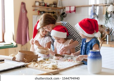Family is cooking Christmas gingerbread cookies in cozy home kitchen for holiday dinner. Funny kids and woman bake Xmas biscuits. Mother is teaching daughters. Lifestyle moment. Children chef concept.