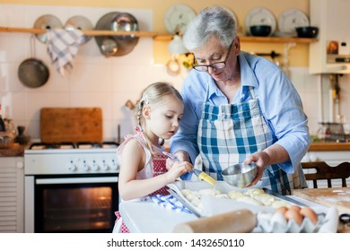 Family is cooking in cozy home kitchen. Grandmother and child are using oven. Senior woman and little child girl are baking pastries. Cute kid is helping to prepare for dinner.
