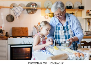Family is cooking in cozy home kitchen. Grandmother and child are using oven. Retired woman and little girl are baking french pastries. Cute kid is helping to prepare dinner. Children chef concept.