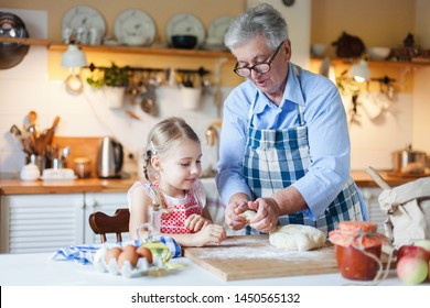 Family is cooking in cozy kitchen at home. Grandmother is teaching little girl. Senior woman and child make pastry dough together. Cute kid is helping to prepare meal for Thanksgiving Day dinner.