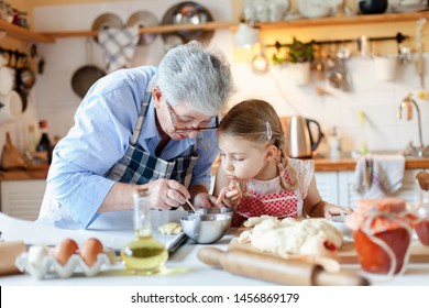 Family is cooking in cozy kitchen at home. Grandmother and child are making italian food and meal. Senior woman and little girl are baking. Cute kid is helping to prepare dinner. Children chef concept