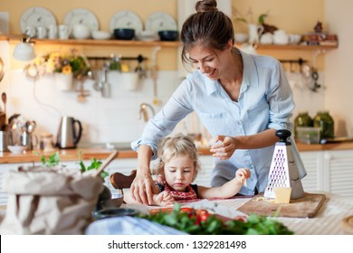 Family are cooking italian pizza in cozy home kitchen. Happy mother is teaching cute kid to prepare food or meal for Thanksgiving dinner. Little girl is helping woman. Children chef concept.
