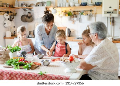 Family are cooking italian pizza together in cozy home kitchen. Cute kids, mother and grandmother are preparing food for dinner. Women are teaching three girls. Cooking class, children chef concept.