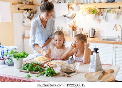 Family are cooking italian pizza together in cozy home kitchen. Cute kids with happy mother are preparing food for dinner and eating cheese. Two girls are helping woman. Lifestyle moment.