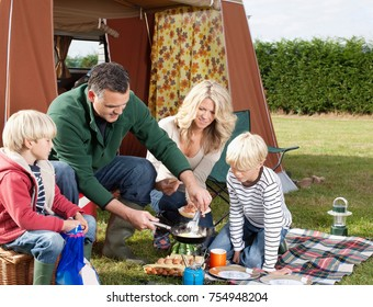 Family cooking meal outdoors