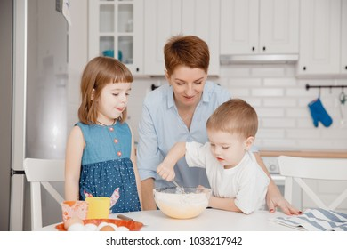 Family cooking. Mom with children preparing dough for cupcakes, boy - young assistant