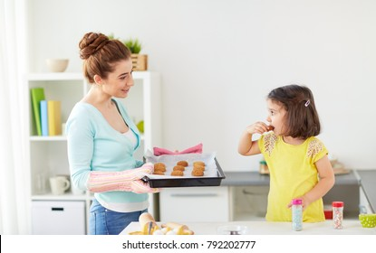 family, cooking and people concept - happy mother holding tray and little daughter eating cookie at home kitchen