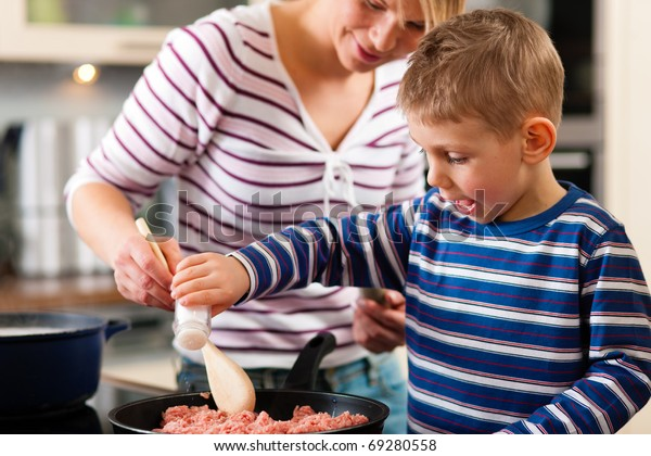 Family cooking in their kitchen - mother making some spaghetti sauce, son is putting some salt in