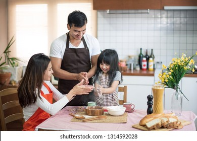 The family cooks. Daughter, Mother and Father prepare dough powder. All have aprons. Live at home in the kitchen. They enjoy and smile.