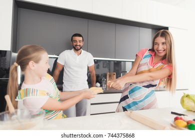 The family cooks dough for baking. Mom and the girl are preparing a dough, they fool around and tore it up. The father stands by and watches. They are in a modern kitchen at home.