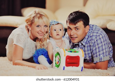 the family cosiness, mother and the father embrace the baby