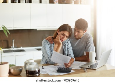 Family couple having many bills and debts: attractive woman with sorrorful expression looking at bill not knowing how to pay it, not having money and her husbamd who trying to calm her, embracing