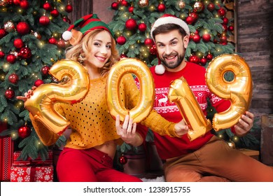 Family couple in love man male  husband and woman female wife in santa hats and red sweater celebreting Merry Christmas Eve and Happy New Year with gold ballons 2019 at home with christmas tree gifts.