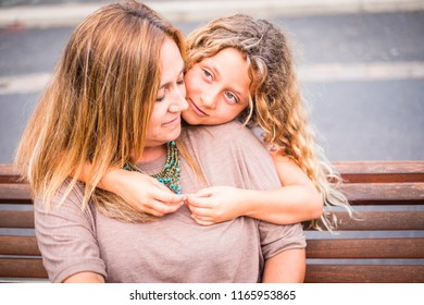 family couple mother and daughter together in outdoor happy leisure activity hugging and enjoying the day of summer before the back to school and the winter. blonde caucasian mom and girl