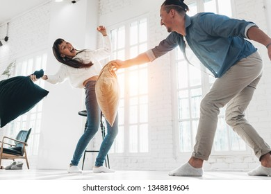 Family couple pillow fighting and playing fool together in bright and spacious apartment