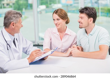Family couple sitting in doctor's office at consultation.