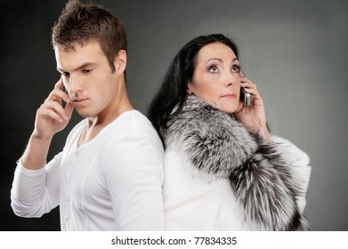 Family couple speak on mobile phones, on gray background.