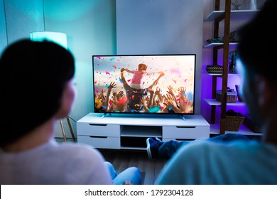 Family Couple Watching TV Or Movie On Couch