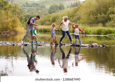 Family Crossing River Whilst Hiking In UK Lake District