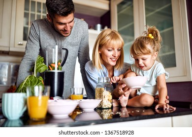 Family with cute girl having breakfast in kitchen