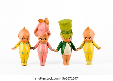 Family of cute miniature vintage celluloid dolls holding hands on a white background