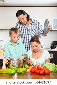 Family cutting the vegetables for salad in home kitchen