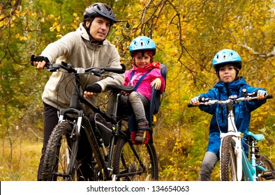 Family cycling outdoors, golden autumn in park, farher and kids on bikes, family sport