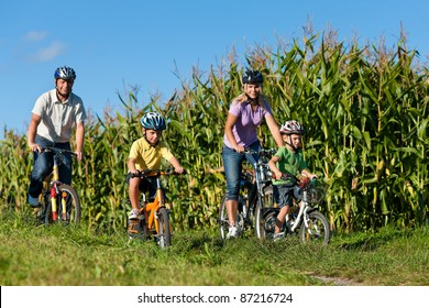 Family is cycling in summer - father, mother and two sons