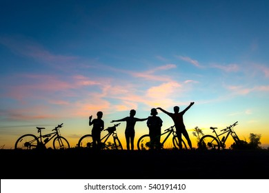 Family cyclist and Bicycle silhouettes on the dark background of sunsets