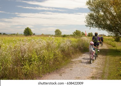 Family cyclo holidays, father and daughter in tandem. The tourist (bike) itinerary of Grado (Friuli Venezia Giulia region of Italy). Family, education, recreation and sport concept