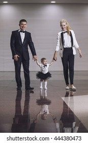 Family, dad, mom and daughter stylish and fashionably dressed beautiful and happy together