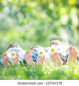 Family with daisy flowers lying on green grass against spring blurred background