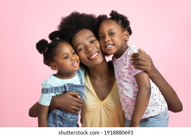 Family day concept. Close up studio portrait of happy young dark skinned mommy with her cute little two daughters, smiling, hugging and having fun together, on isolated pink background