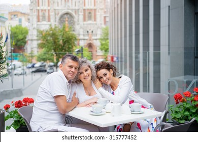 Family day. Elderly loving couple and their adult daughter smiling at camera while sitting in sidewalk cafe.
