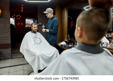 Family day. Father and son are sitting in armchairs and looking at each other while visiting barber shop together. Getting haircut. Barbershop, hairsalon, haistyle