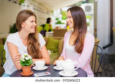 Family day. Two adult sisters talking while drinking tea at cafe.